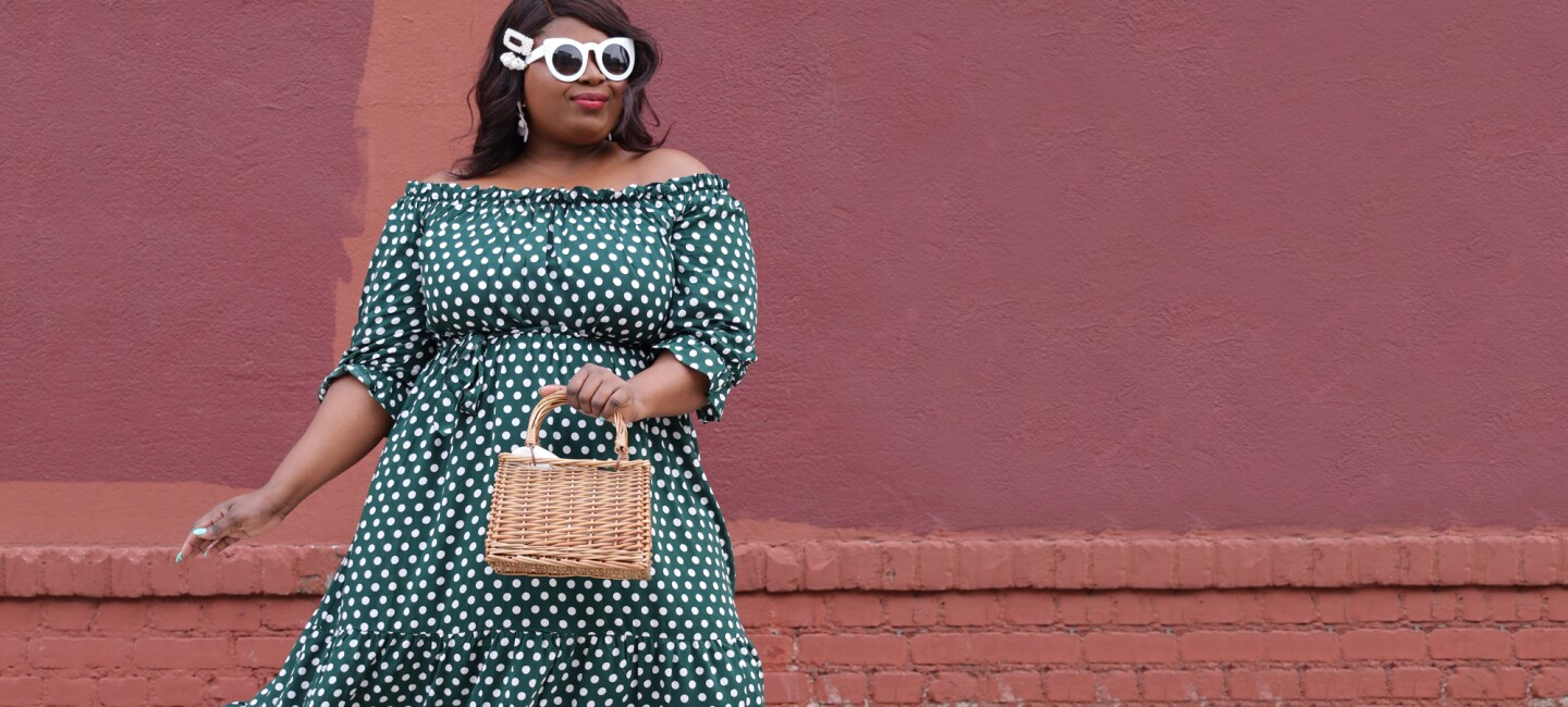 A stylish plus-sized, dark-skinned woman in front of a brick and stucco wall wears an off-the-shoulder dress with white polka dots, white retro sunglasses, and carries a small wicker purse.