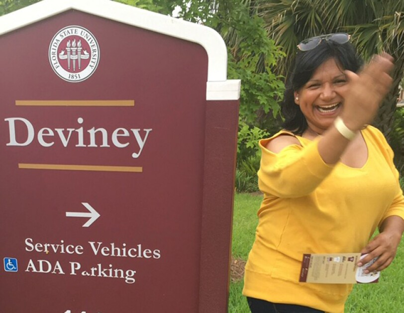 A smiling woman stands next to a Florida State University sign.