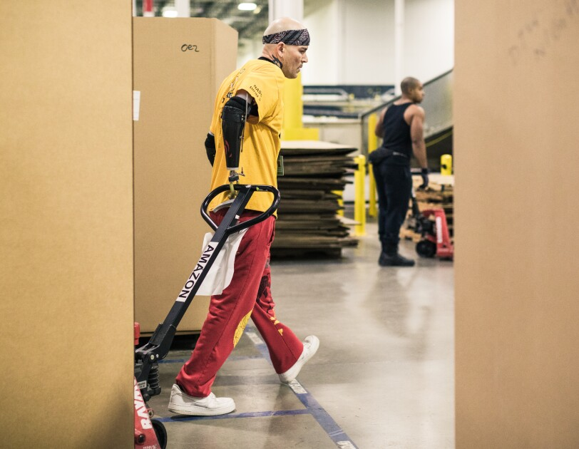 A man with dual arm prosthetics uses a pallet jack to pull a large box. He wears a yellow Amazon branded t-shirt.