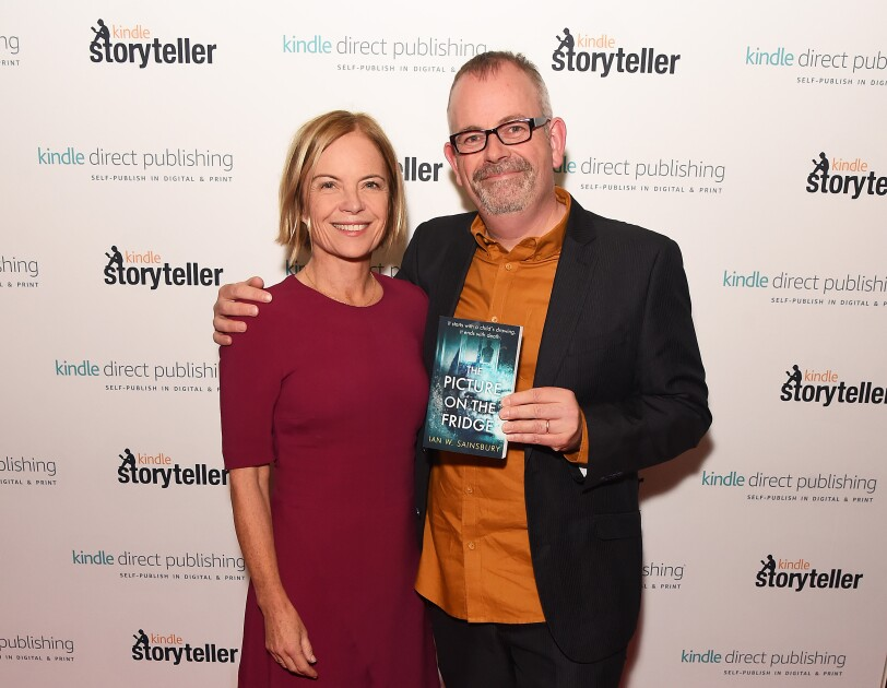 Ian W. Sainsbury standing with Mariella Frostrup (judge for this year's Kindle Storyteller) holding his book in front of press wall at the Amazon Kindle Storyteller Awards.