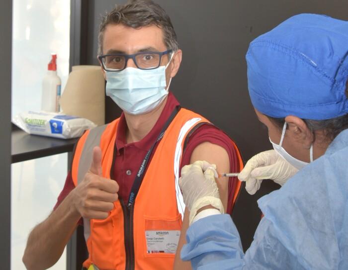 Un dipendente Amazon alza il pollice della mano destra in segno di OK mentre riceve il vaccino contro il Covid-19. L'operatrice sanitaria che sta somministrando la dose è ripresa di spalle, e indossa una tuta protettiva blu.
