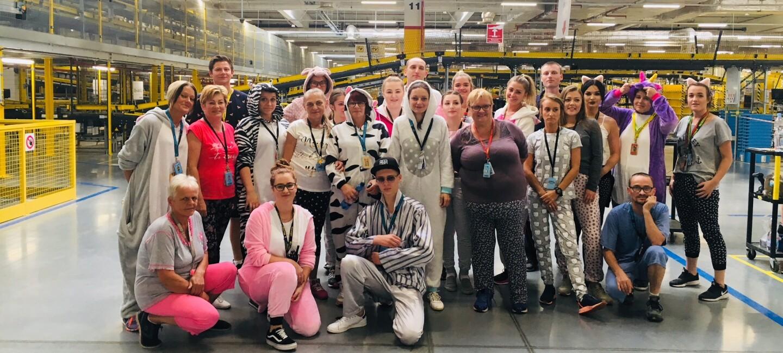 Pracownicy Amazon z młodymi odwiedzającymi centrum logistyki