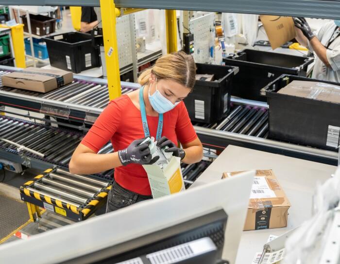 L'immagine mostra una donna dipendente amazon all'interno del magazzino che ispeziona  i prodotti resi e li valuta