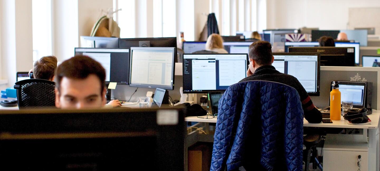 Großraumbüro am Standort in Berlin. Schreibtische mit Bildschirmen und arbeitenden Menschen.
