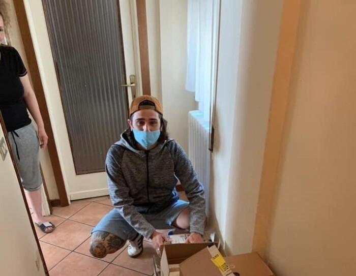 Un ragazzo sistema alcune scatole in un corridoio. Indossa una mascherina sul viso e un cappello in testa. E' inginocchiato per terra davanti alle scatole.