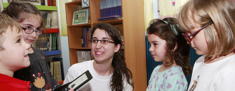 Una asociada de un centro logístico observa sonriendo la cara de sorpresa de cinco alumnos de una escuela de primaria beneficiaria de una Kindle Donation. Ella está arrodillada y los cuatro pequeños tienen un Kindle entre las manos.