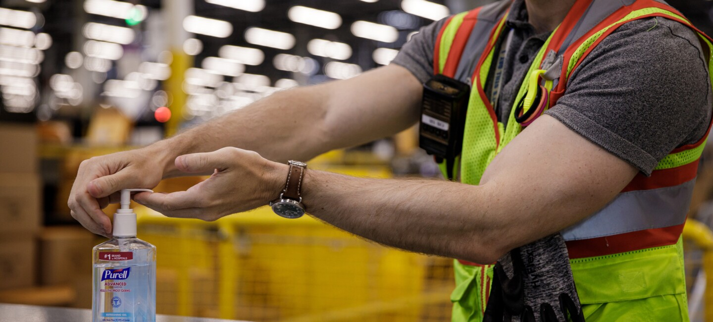 A man in a safety vest pumps sanitizer into his palm.