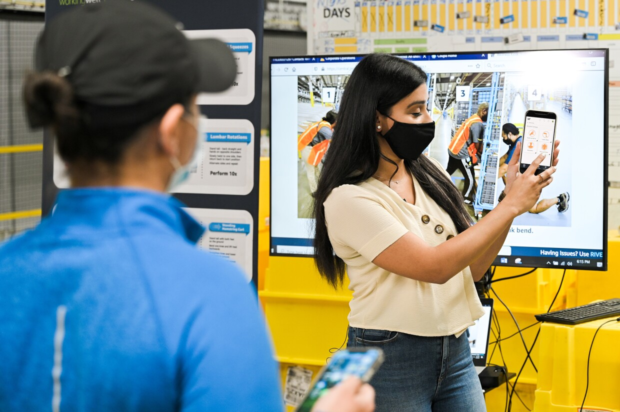 An image of an Amazon employee in a fulfillment center demonstrating how WorkingWell works.