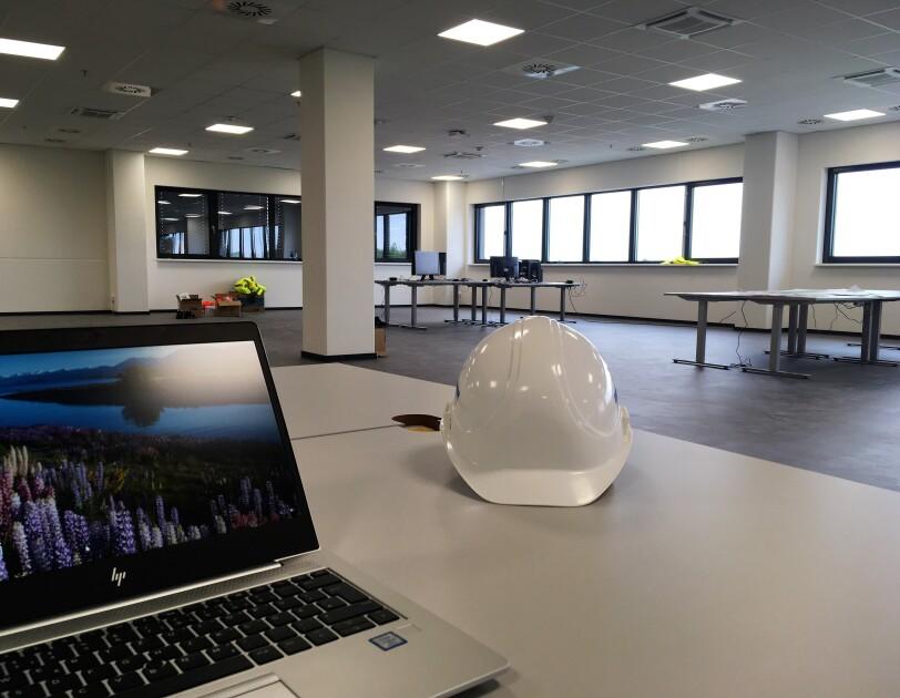 Auf einem weißen Schreibtisch steht links ein Laptop, rechts ein weißer Bauhelm. Im Hintergrund Schreibtische mit einigen Bildschirmen. Die Bürofläche ist noch nicht fertig eingerichtet.