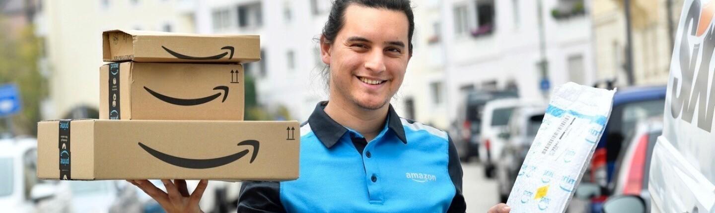 Ein junger Amazon Fahrer im blauen Amazon-Shirt stellt Pakete zu.
