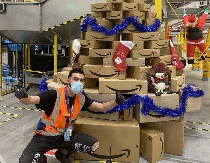 Adorno navideño de BCN8.  Un árbol de Navidad hecho de cajas. En la parte superior tiene una estrella roja y decoración de color azul brillante. Delante del árbol hay un asociado casi de rodillas haciendo con las manos con guantes la señal de victoria. Lleva unos pantalones negros con agujeros en las rodillas, una camiseta negra de manga corta y un chaleco naranja.