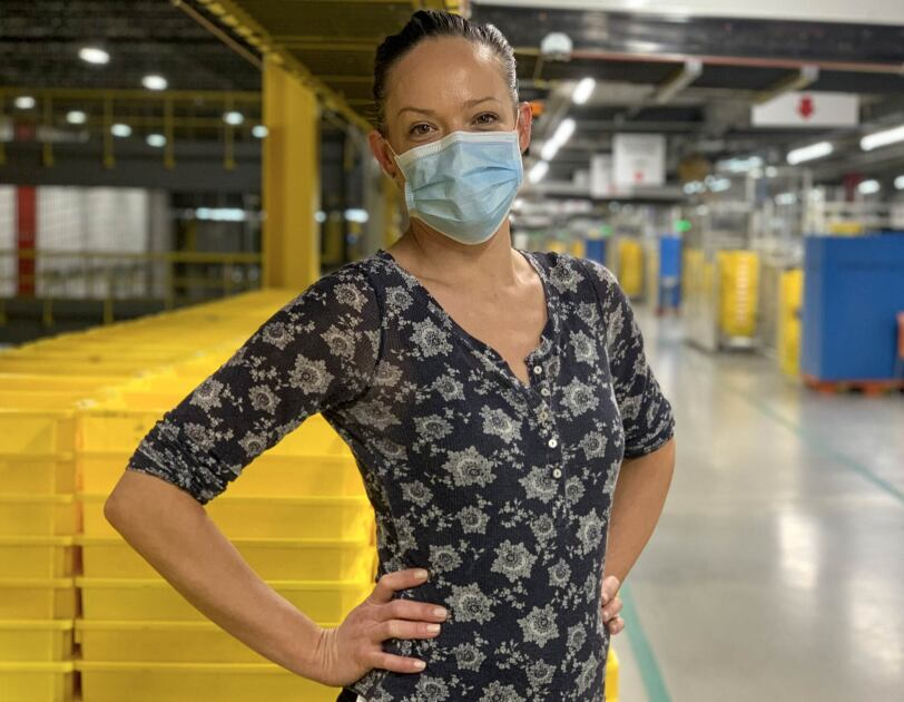 A woman wearing a mask stands in front of stacks of yellow plastic boxes.