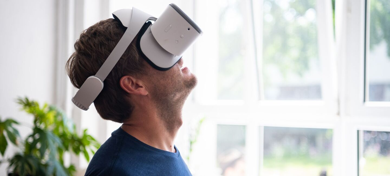 Ein Mann sitzt vor einem hellen Fenster und schaut begeistert durch seine VR-Brille