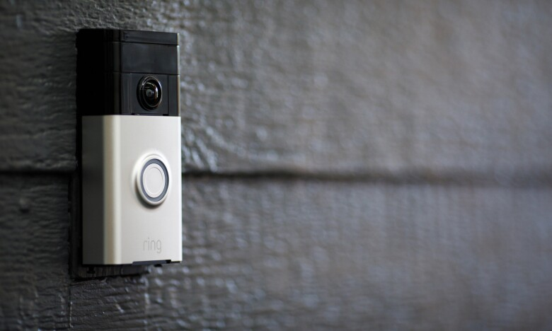 A Ring video doorbell on a black wall.