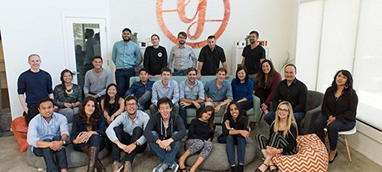 Un groupe d'une vingtaine de personnes se tient assis sur et autour d'un canapé, devant le logo d'une entreprise