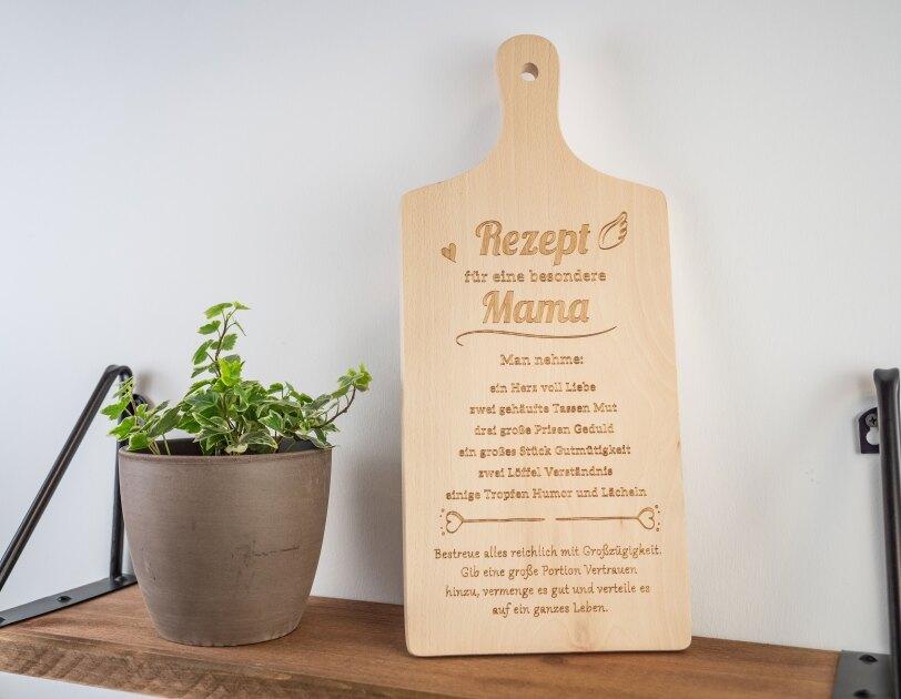 """Auf einem Regal steht ein Holzbrett mit der Aufschrift """"Rezept für eine besondere Mama"""""""