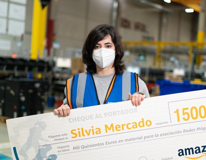 Silvia Mercado es la cuarta ganadora de una Amazon Dream Box en España. Silvia está sujetando un cheque de 1 500 euros para material para la asociación Rodes màgiques. De fondo hay un centro logístico con estanterías de color amarillo. Silvia lleva el pelo  negro por el hombro y escalonado. Su jerseiy es de color gris y lleva un chaleco de Amazon Box Star de color azul.