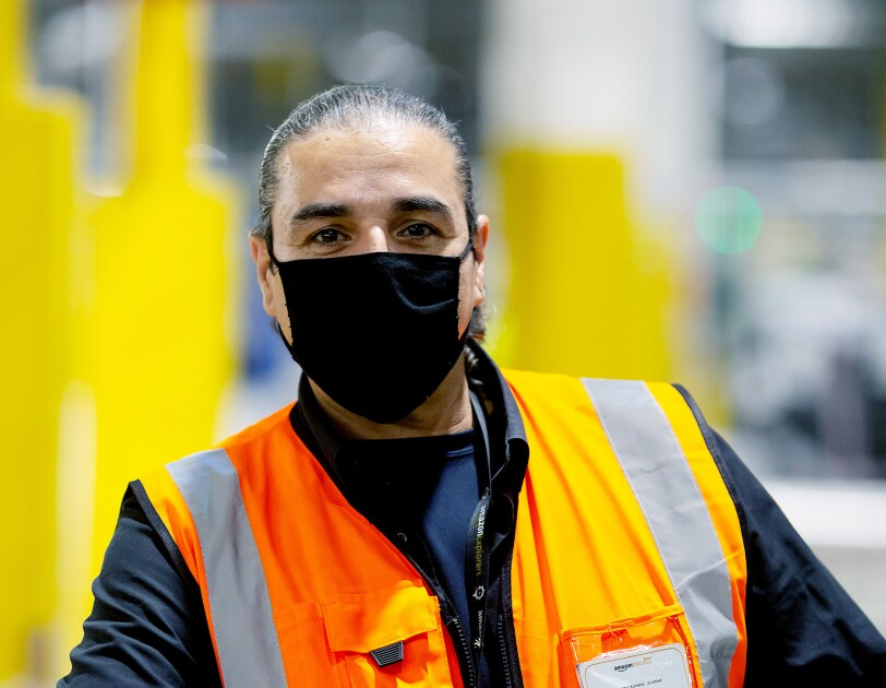 Antonio Kanaris - wearing a facemask and hi-vis in a fulfilment centre.