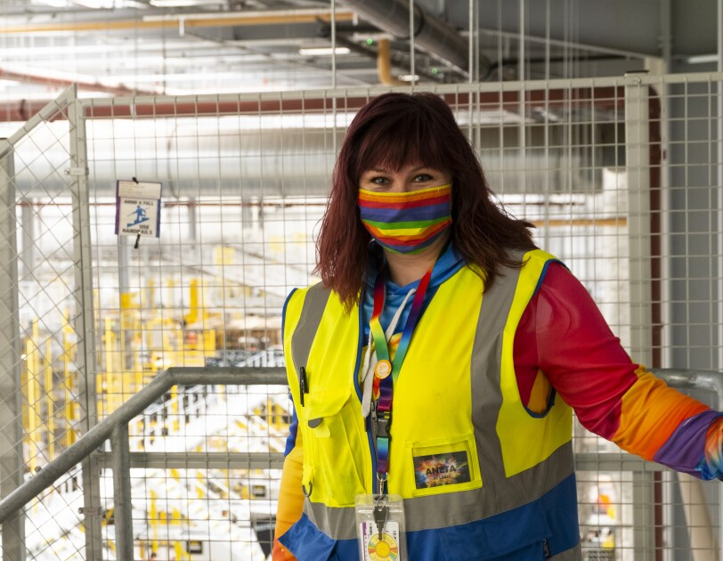 Amazon FC Lead Aneta Bachledova-Pateman wearing a yellow vest and a rainbow face mask, inside an Amazon site