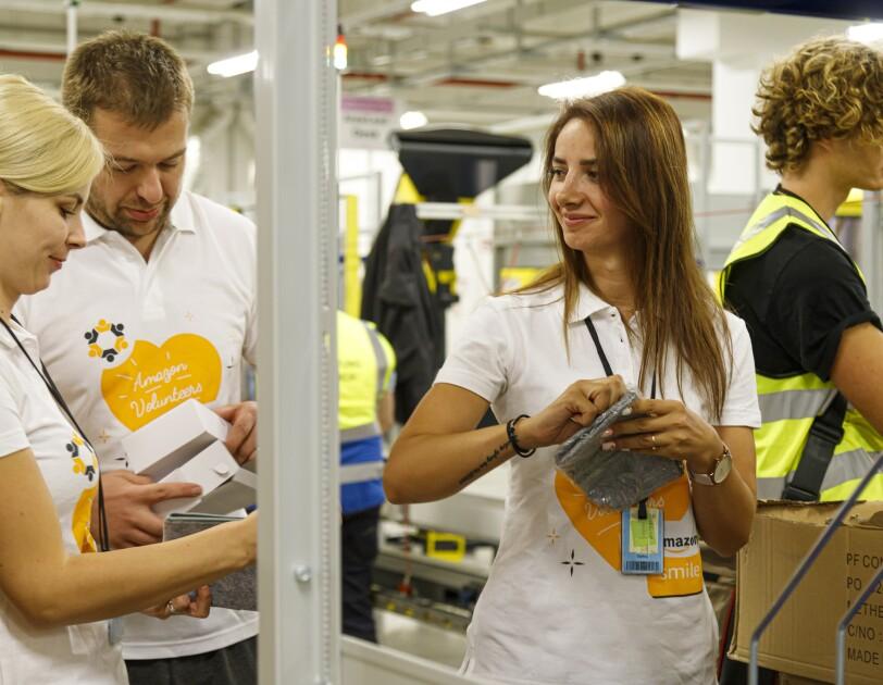 """3 Mitarbeiter in T-Shirts mit Aufdruck """"Amazon Volunteers"""" beim Packen."""
