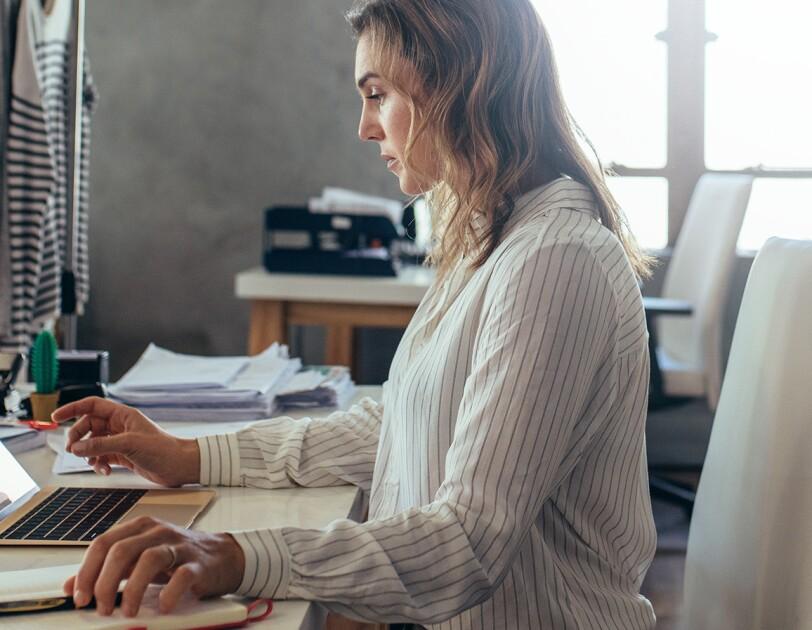Blonde Frau sitzt am Tisch und arbeitet am Laptop. Im Hintergrund sieht man Stoffe und Kleiderstangen.