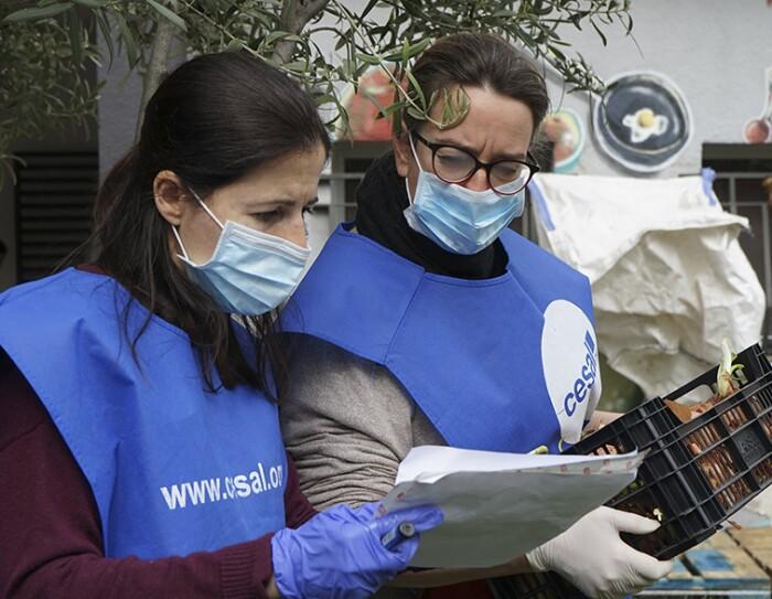 Con el proyecto Stop Coronavirus la ONG Cesal atiende a más de 400 familias en Madrid. Dos voluntarias con el chaleco de Cesal, guantes y mascarilla están mirando el papel que una de ellas sujeta con la mano. La otra sujeta una caja de plásitco de color negro que tiene cebollas. Las dos tienen el pelo largo y la que sujeta la caja de cebollas lleva gafas. Están en el exterior.