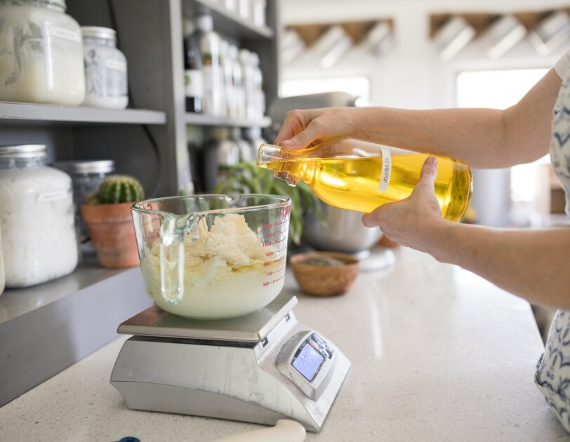 A woman pour's jojoba oil into a large, glass measuring cup on a scale. Other ingredients for soap making are already in measuring cup. Behind the mixture are jars of ingredients for the company's soaps and candles.