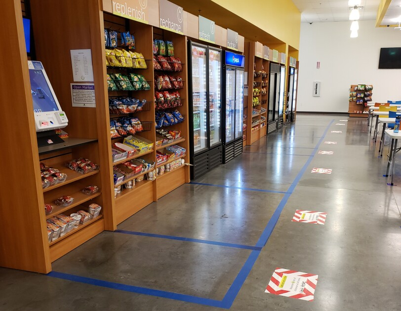View inside an Amazon fulfillment center break room. Lines are taped on the floor to illustrate where associates should stand in order to maintain social distancing with the person in front of them.