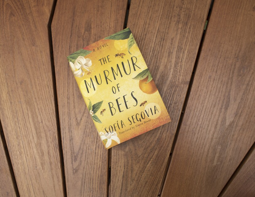 """Book cover for """"The Murmur of Bees"""" on a teak wood background."""