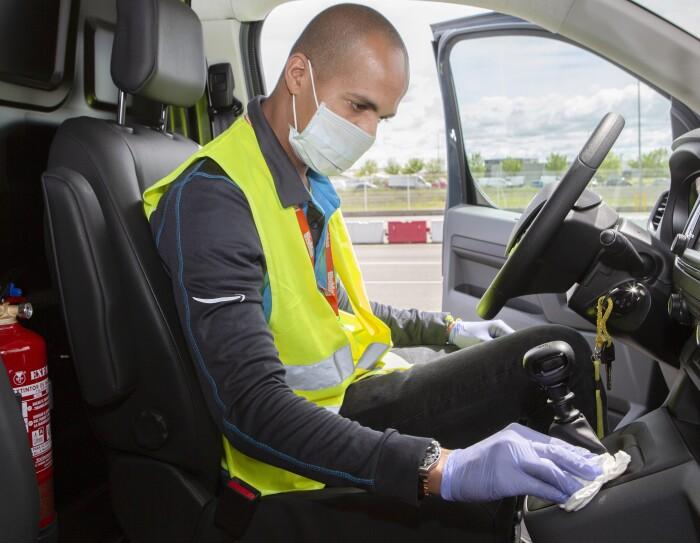 Un conductor con guantes, mascarilla y chaleco amarillo está limpiando el cambio de marchas. Tiene la puerta abierta. La furgoneta es de color gris.
