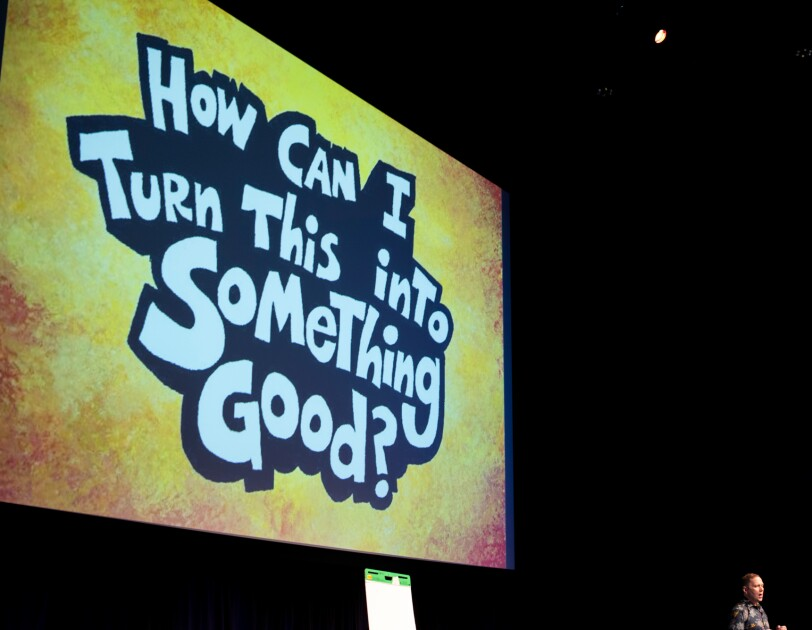 "A man on a stage stands in front of a large screen displaying the words ""How can I turn this into something good?"""