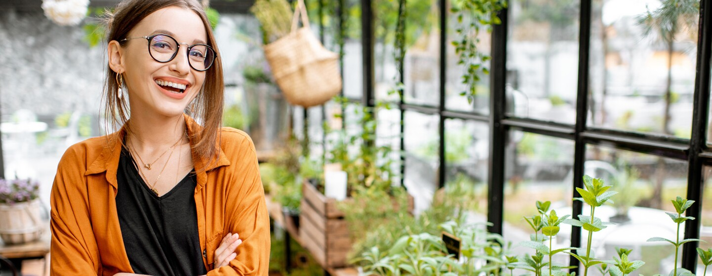 A woman smiles from inside a green house, her arms crossed.