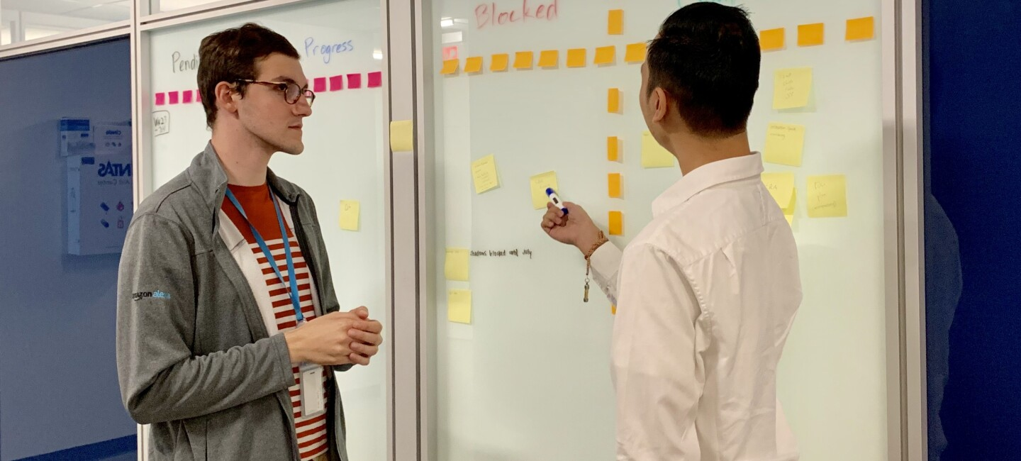 Two men stand together, working on a whiteboard in an Amazon office.