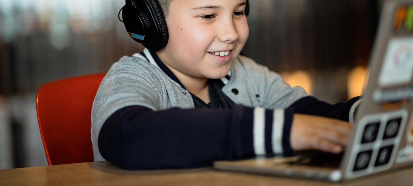 A smiling boy wearing headphones types on a laptop computer.