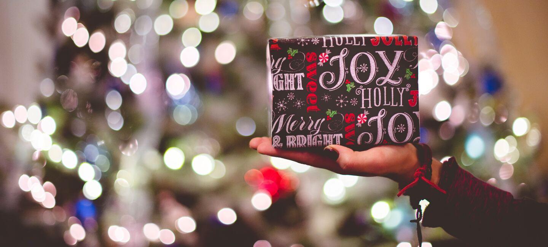 Eine weibliche Hand hält ein hübsch verpacktes Weihnachtsgeschenk. Im Hintergrund stehe ein hell leuchtender Weihnachtsbaum.