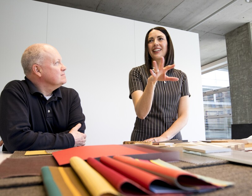 A woman in a grey-striped shirt stands over fabric swatches, talking with a male colleague, her right hand extended in front of her.