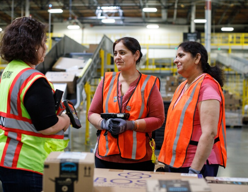Three women in safety vests stand in a warehouse space.