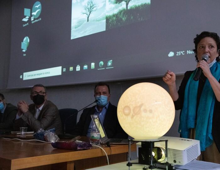 Foto di una donna di fronte ad un proiettore ed una riproduzione in miniatura della luna, illuminata.