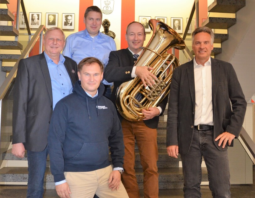 Gruppenbild mit vier männlichen Personen. In der Mitte steht der Bürgermeister mit der Tuba.