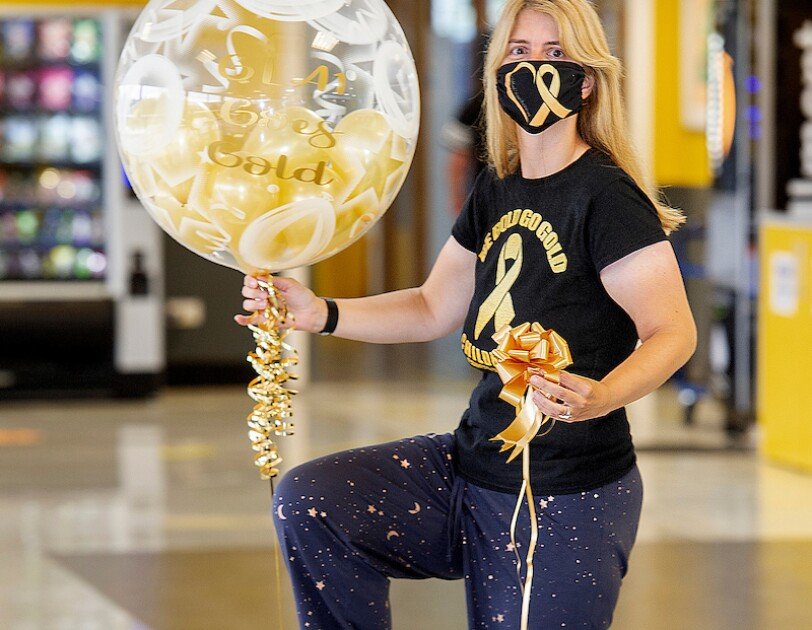 Amazon employee stood on one leg holding balloons and dressed in PJ's