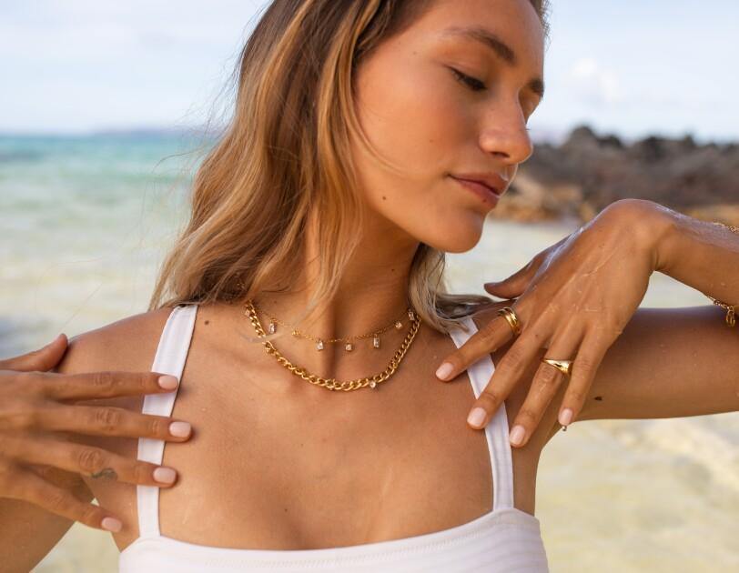 Eine Frau mit blonden Harren präsentiert goldenen Ketten und Ringe.