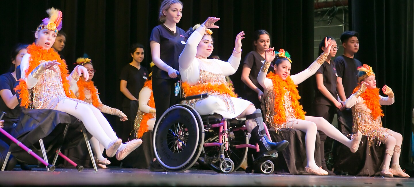 Students at Dancing Dreams, performing on stage in their recital. Many of the students have aides to support them.