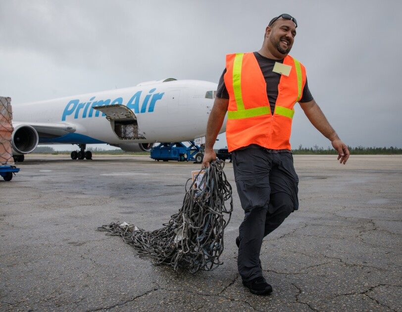 A man in a safety vest works with a cargo plane in the background.
