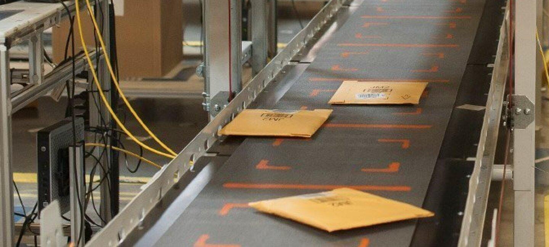 Des enveloppes prêtes à être livrées défilent sur un tapis roulant dans un centre de distribution Amazon