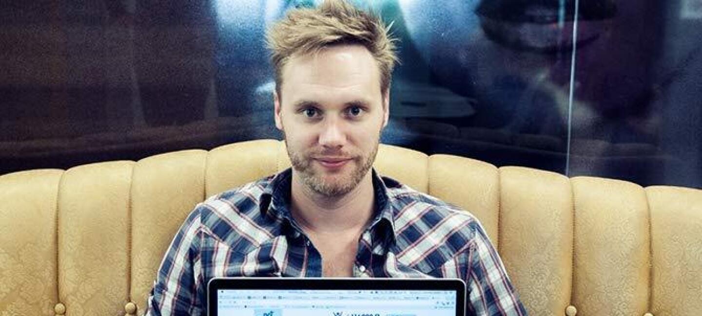 Laurent Dochy est assis sur un canapé et montre sur un ordinateur portable la page web du site NotFound où apparait une vidéo sur les enfants disparus