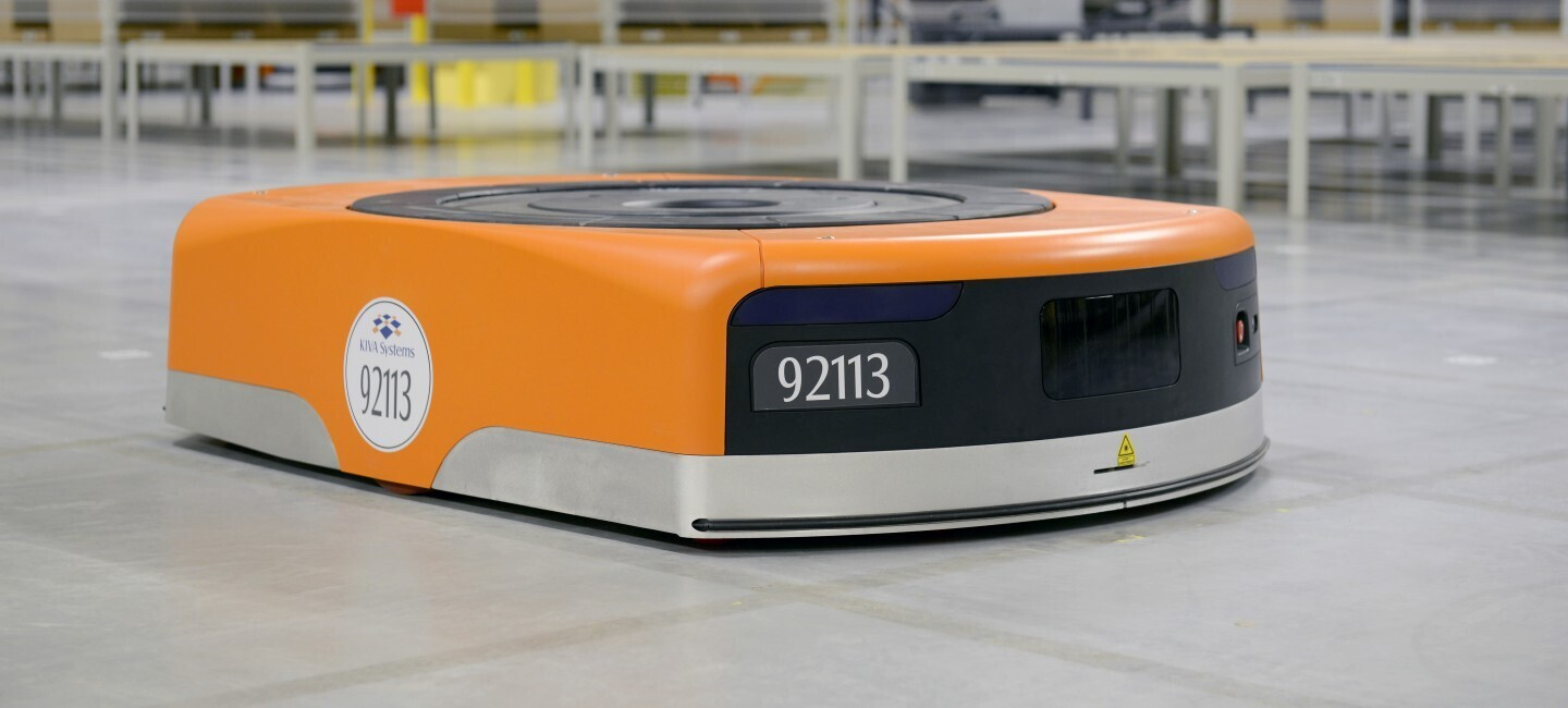 The image of an Amazon robot, in the shape of a thick disk moving on the ground. Its color is orange and black, the code number is 92113.