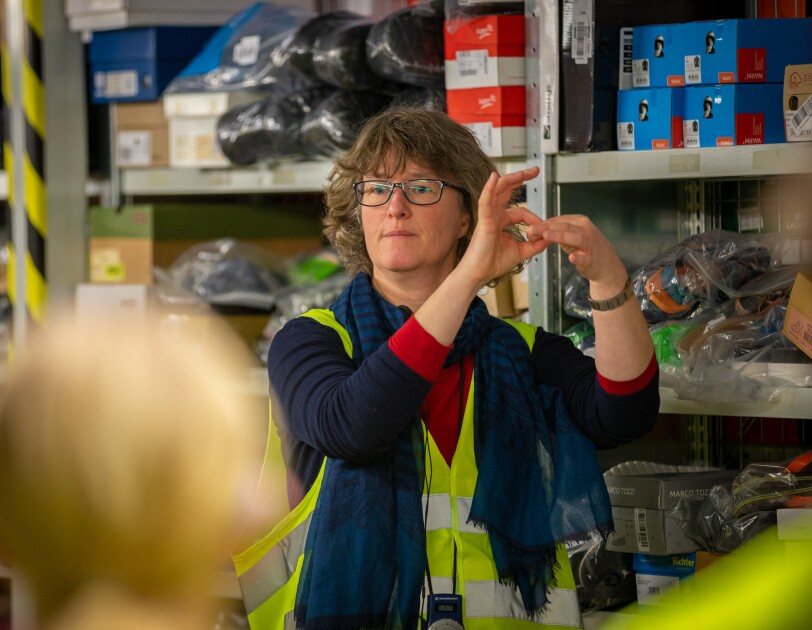 Eine Frau mit Brille übersetzt in Gebärdensprache.