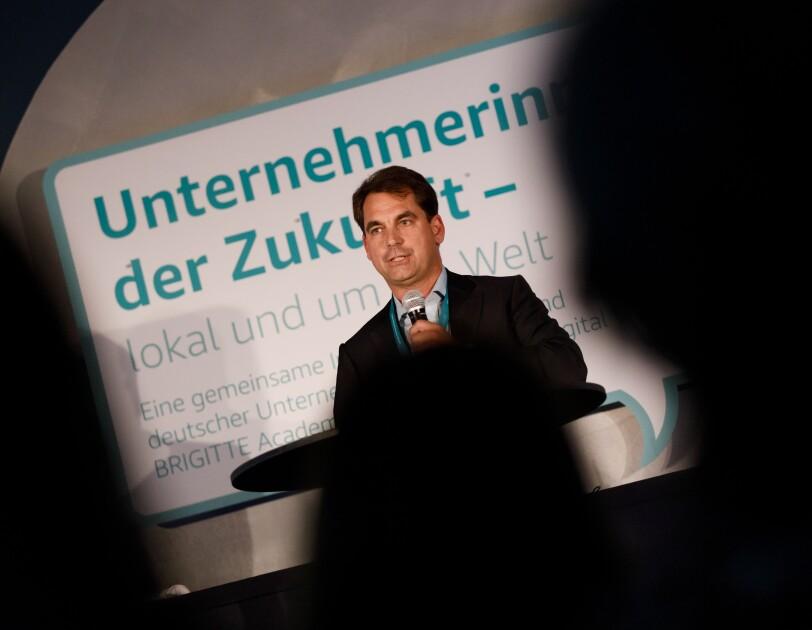 Nicholas Denissen steht auf der Bühne am Rednerpult. Er hält eine Laudation. Er ist aus dem Publikum heraus fotografiert worden. Im Vordergrund sind unscharfe Köpfe des Publikums zu erkennen.