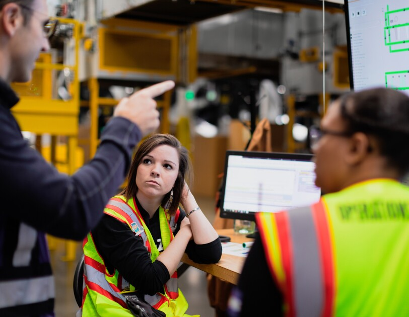 Two women in safety vests sit near computer screens and talk with a man.