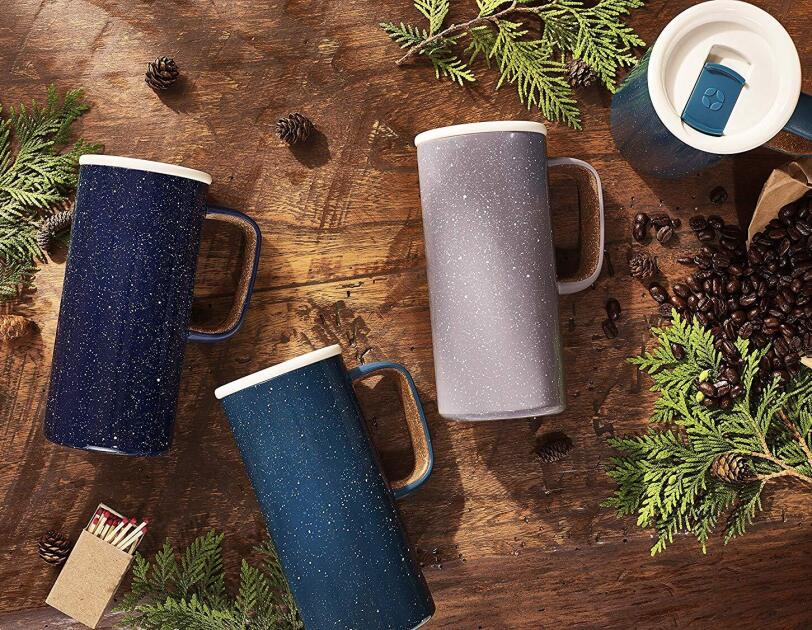 Three tall travel mugs lie on their side, on a rustic wood backdrop. They're surrounded by pine branches, pine cones, and coffee beans. A fourth mug stands in the upper right corner, sealed with a lid.